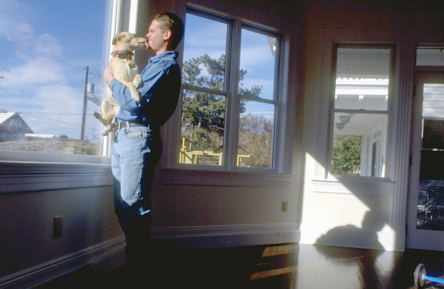 Craig Biggio gets his face licked as he looks out the window of his living room.