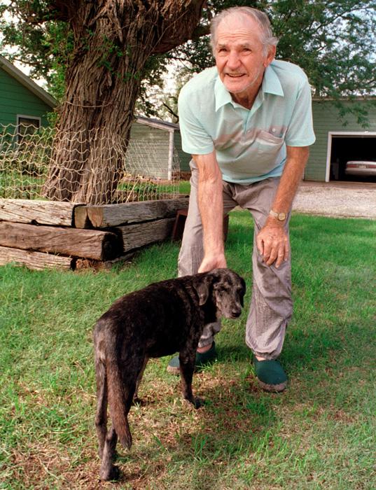Sammy Baugh pets his dog Cow Patty at his West Texas ranch near Rotan, Texas.