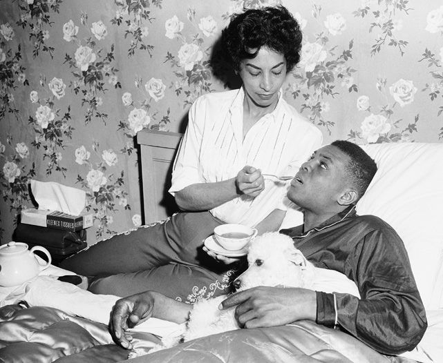 Willie Mays is comforted by his wife Marguerite and dog Pope after catching a virus during spring training in 1957.