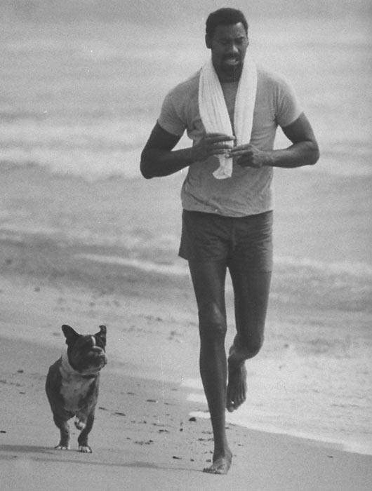 Wilt Chamberlain jogs on a California beach with his dog.