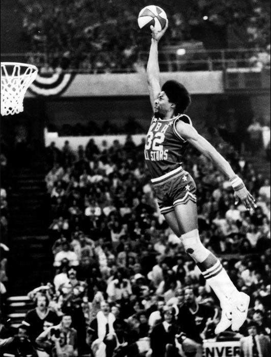 Erving goes for a dunk from the free-throw line during the inaugural slam dunk contest during halftime of the ABA All-Star Game in Denver.