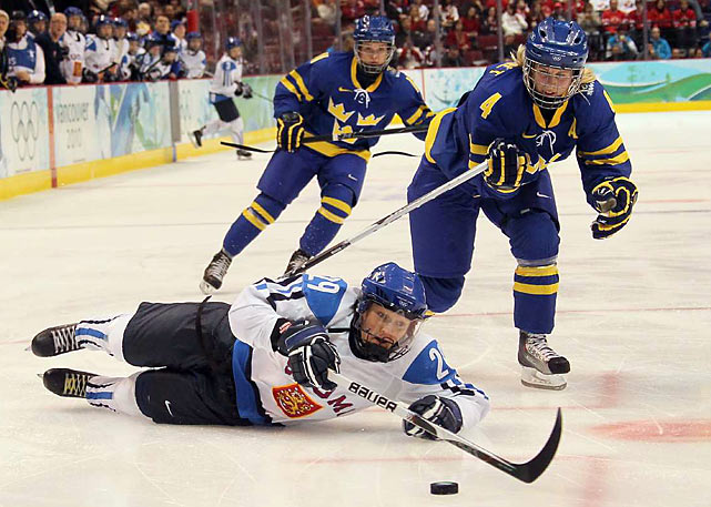 Karoliina Rantamaki (29) and Jenni Asserholt (4) battle during the women's semifinal. Finland won its first medal in women's hockey in overtime during its matchup against Sweden.