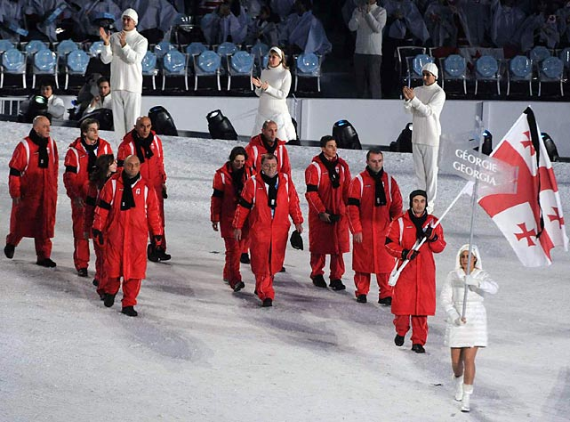 The seven remaining members of the Georgian team, who decided to stay and compete, wore black armbands as they marched behind a black-trimmed flag. Most of the crowd rose to give respectful applause.