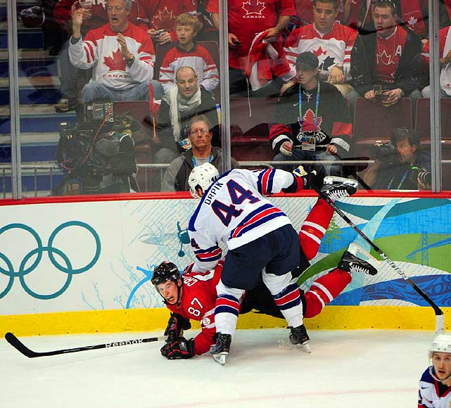 American defenseman Brooks Orpik checks his NHL teammate on the Penguins, Canadian Sidney Crosby, along the boards.