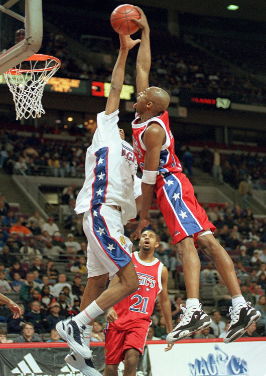 A member of the East team, Bryant shoots over the West team's Jamaal Magloire during Magic's Roundball Classic at The Palace of Auburn Hills, Mich., in April 1996.