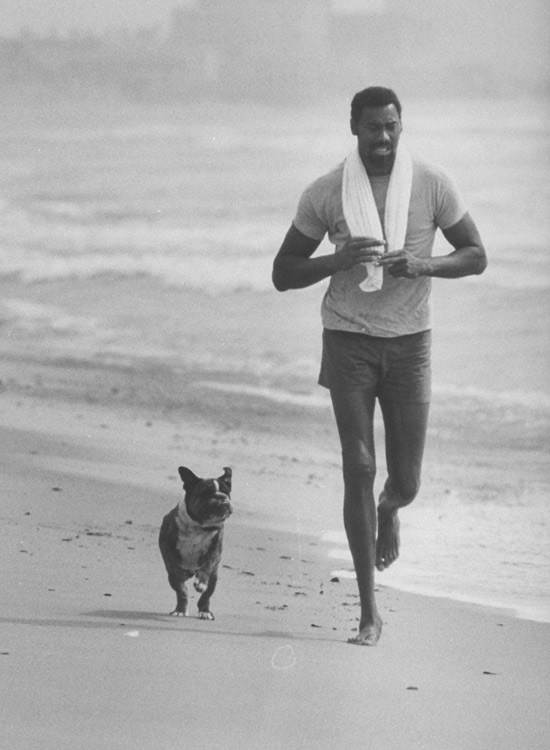 Wilt and his dog take a jog along the beach in California. Keeping up with Chamberlain's long strides couldn't have been easy for a dog.
