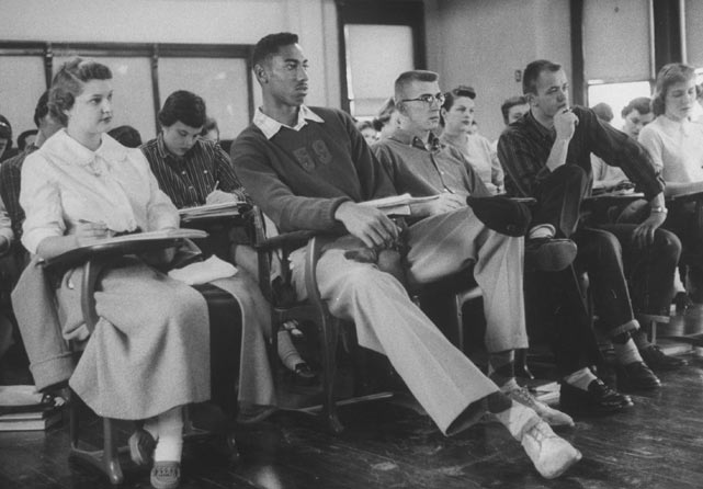 Barely able to fit his 7-foot-1 frame under the desk, Chamberlain is seen here sitting in class at the University of Kansas in 1957. Chamberlain would play for the Jayhawks and also become a member of Kappa Alpha Psi fraternity while at Kansas.