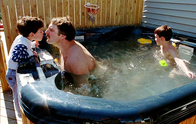 Three-time Olympic medalist Bruce Baumgartner rubbed noses in his hot tub with sons Bryan and Zachary at his home in Cambridge Springs, Pa.