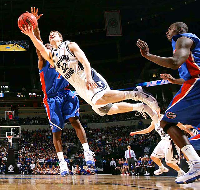 BYU's Jimmer Fredette shoots as he falls in front of Florida guard Kenny Boynton in a first-round game won by in double overtime by BYU, 99-92.