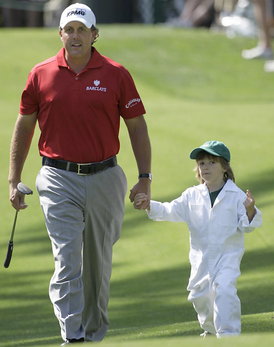 Phil Mickelson walks with his five-year-old son, Evan, to the second green during the par three tournament prior to the 2008 Masters.