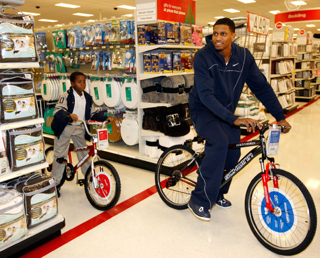 Rudy Gay helps a young child shop for a bicycle during a holiday shopping spree at a Memphis Target.