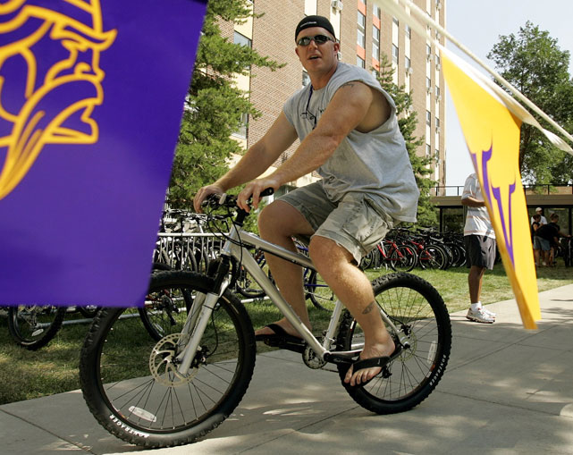 Vikings center Matt Birk is framed by Vikings flags as he arrives at training camp in Mankato, Minn.