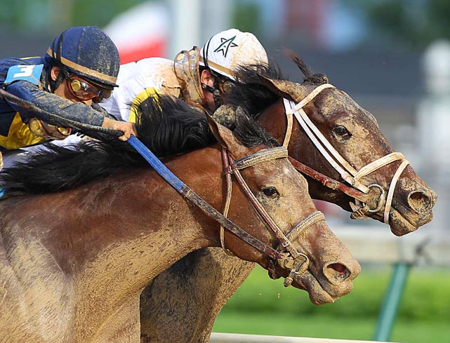 Super Saver with jockey Calvin Borel on board (back with white cap) heads into the final turn next to Noble's Promise with jockey Willie Martinez on board during the 136th Running of the Kentucky Derby. Super Saver won the race, giving Borel three Derby wins in four years.