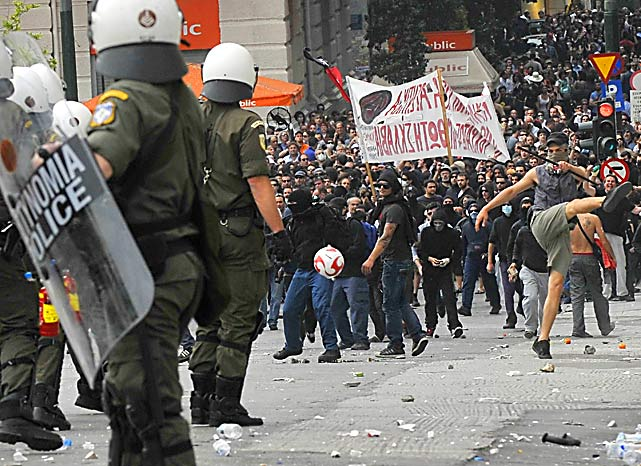 Riot police face demonstrators, including one kicking a soccer ball at them during a massive demonstration on May 5 in Athens.