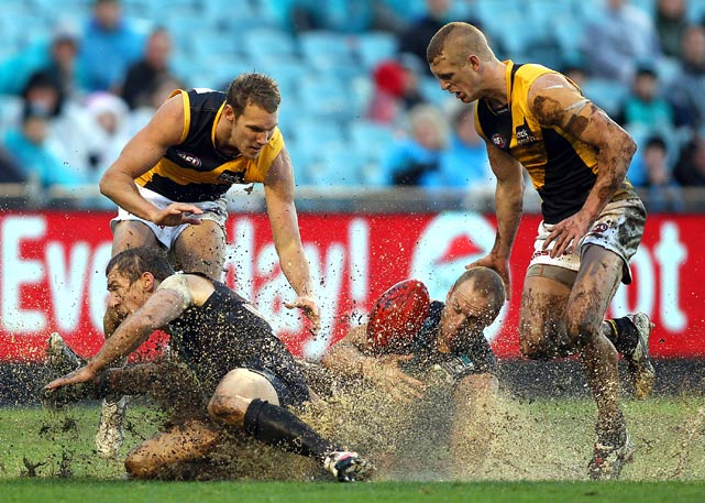 Brett Ebert and Chad Cornes of the Port Adelaide Power slide in the mud with Kelvin Moore of the Richmond Tigers during their round 10 AFL match at AAMI Stadium May 29 in Adelaide, Australia. Richmond defeated Port Adelaide 77-30.