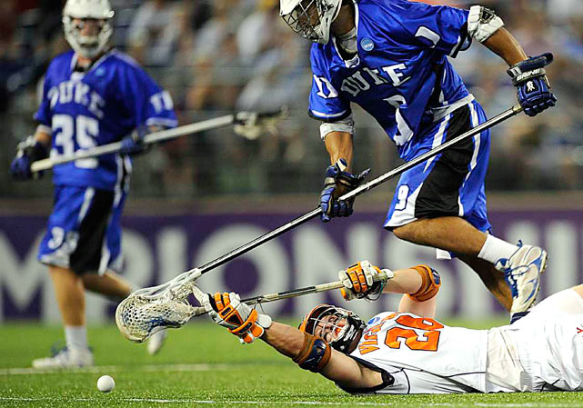 Virginia's Brian McDermott, bottom, eyes the ball after being tripped by Duke's CJ Costabile during the second half of Final Four semifinal May 29 in Baltimore. Duke won 14-13.