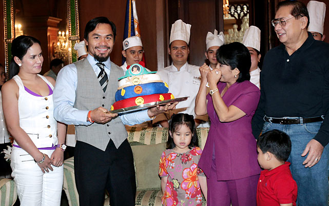 Pacquiao holds a cake while Philippine President Gloria Arroyo gestures during a courtesy call at the Malacanang Palace in Manila.