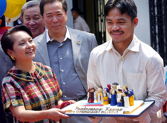 Phillipines President Gloria Arroyo presents Pacquiao with a commemorative cake after his unanimous decision victory over Marco Antonio Barrera.