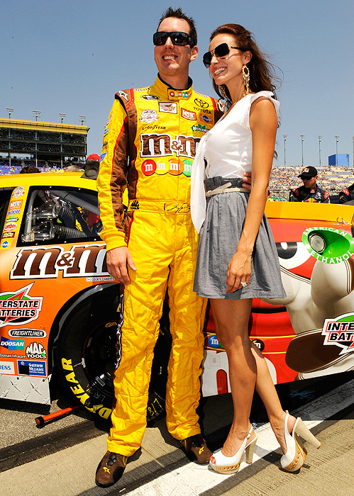 Kyle Busch and his wife Samantha Sarcinella pose for photos before the start of the STP 400 at Kansas Speedway.