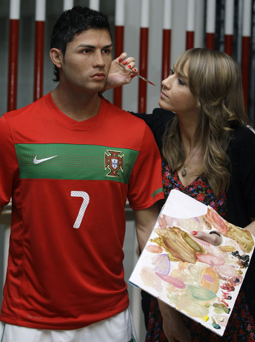A makeup artist works on the new wax figure of Ronaldo as it is unveiled at Madame Tussauds in London.