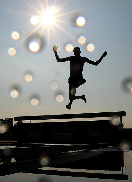 Water droplets hit the lens of the camera as a competitor passes over the water jump in the 3000m steeplechase during the IAAF Diamond League at Icahn Stadium on June 12 in New York City.