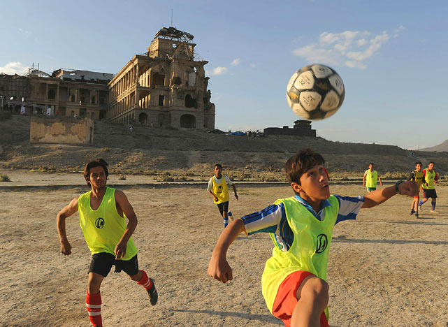 Afghan youth play soccer in front of the war-damaged Darlaman Palace on June 9 in Kabul.