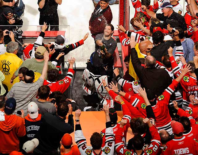 Chicago Blackhawks goalie Cristobal Huet sprays champagne on fans after the Blackhawks defeated the Flyers in overtime of Game 6 to win the Stanley Cup.