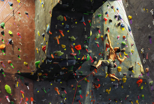 Ivan Greene, a rock-climbing specialist, makes his way up a man-made rock-climbing wall at Brooklyn Boulders, an 1,800-square-foot indoor facility in New York City that includes a climbable replica of the facade of the Brooklyn Bridge.