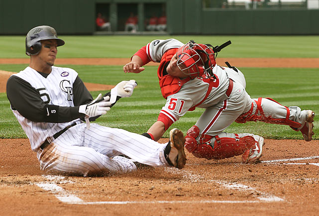 Colorado's Carlos Gonzalez scores on a sacrifice fly as Carlos Ruiz is late with the tag on May 12 at Coors Field in Denver. The Rockies defeated the Phillies 4-3 in 10 innings.