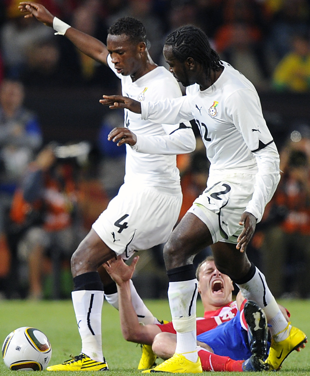 Ghana's defender John Paintsil (left) and striker Prince Tagoe (right) try to step over Serbia's midfielder Milan Jovanovic during their Group D first-round match.