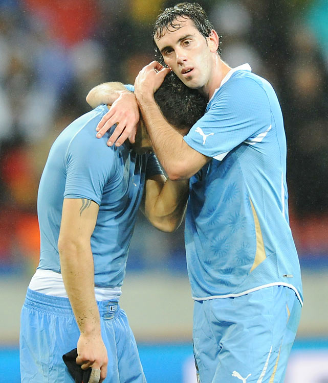 Uruguay's Luis Suarez is consoled by Diego Godin after the match. Suarez, perhaps the most controversial player of the World Cup, scored three times in six matches.