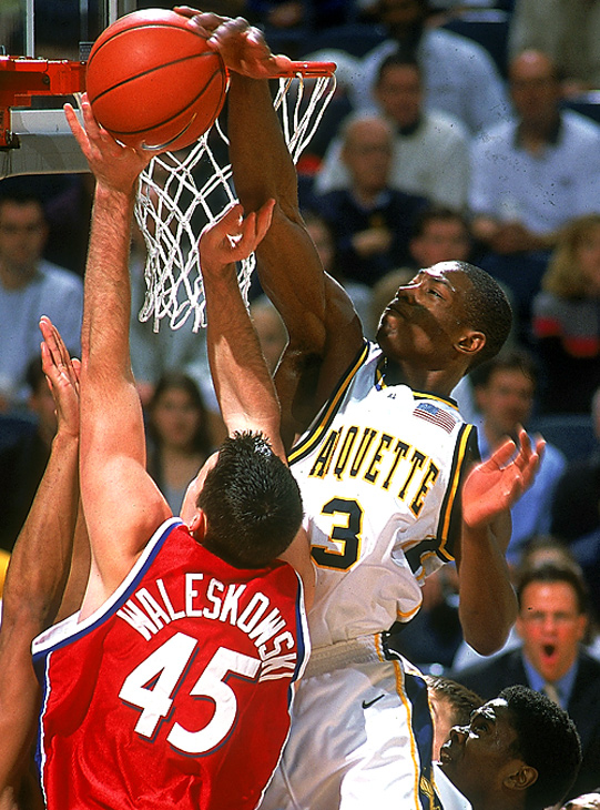 Due to the NCAA's Proposition 48, Wade was ineligible to play his freshman year at Marquette. He was cleared to play his sophomore year and had an immediate impact. In this photo, he shows off his defensive skills by blocking the shot of Dayton's Keith Waleskowski.