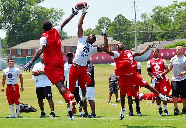 Cornerback Deon Bush (back to camera) and linebacker Jerome Howard leap to break up a pass.