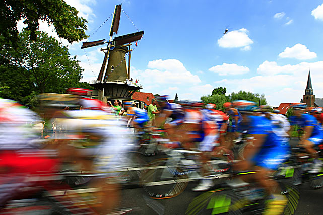 The pack rides past a windmill and spectators during the 138.9-mile first stage of the Tour de France run between Rotterdam, the Netherlands, and Brussels, Belgium, on July 4.