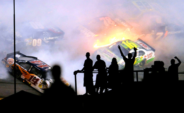 Fans look on as a crash takes place on Lap 148 during the NASCAR Sprint Cup Series Coke Zero 400 at Daytona International Speedway on July 3.  Kevin Harvick won the race.