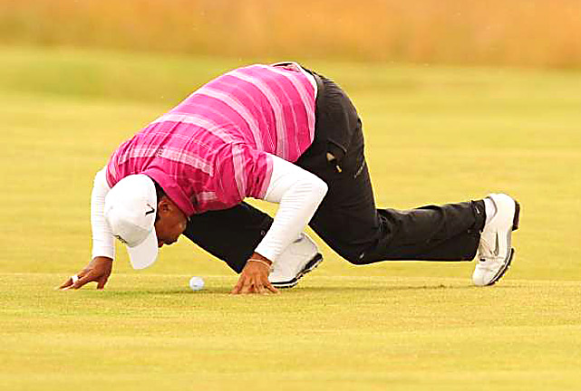 Tiger Woods blows an insect off his ball on the 14th hole during the first round of the 139th Open Championship on the Old Course, St Andrews on July 15 in Scotland.