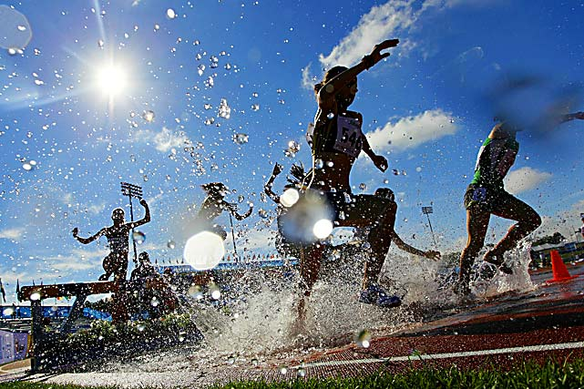 Athletes clear the water jump during the women's 3000-meter steeplechase qualification heats on day two of the 13th IAAF World Athletics Championships in Moncton, Canada.