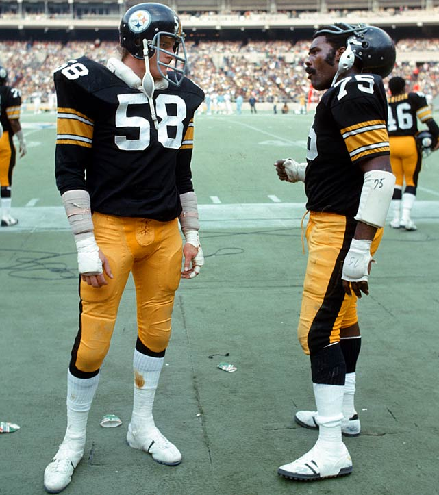 "Steelers linebacker Jack Lambert and defensive tackle ""Mean"" Joe Greene chat before a home game against the Broncos. Lambert had an interception in the game."