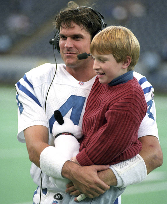 Colts QB Jim Harbaugh holds his son Jay following a victory over the Jets.