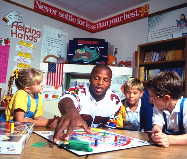 Cardinals fullback Larry Centers plays a board game at a school in Arizona.