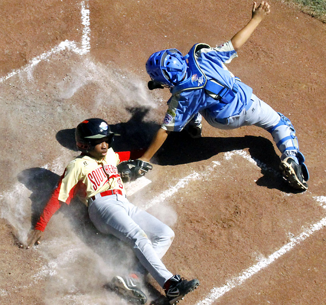 Georgia's Brandon Pugh of Columbus slides around the tag of Hawaii's Kaimana Bartolome. The loss eliminated Georgia.