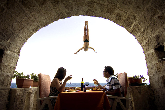 Diners plunged into their pasta as Steve Black of Australia practiced for the Red Bull Cliff Diving World Series in Polignano di Mare on Italy's southern Adriatic coast last Thursday. The town of 16,000 is popular with both pro and recreational divers, who leap from private balconies that line the grotto.