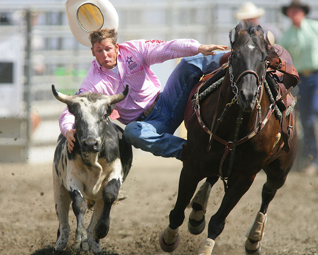 Blake Knowles loses his hat as he scores a time of 12.4 in the Slack Steer Wrestling competition at the Kitsap County Stampede in Bremerton, Washington.