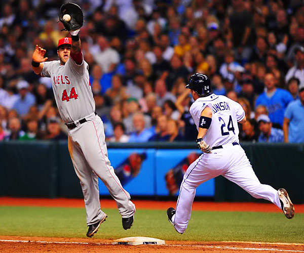 Dan Johnson of the Tampa Bay Rays reaches first on an infield single during the ninth inning as Mike Napoli of the Los Angeles Angels reaches for the high throw. The Angels beat the Rays 6-3 after a tie-breaking, three-run homer from Peter Bourjos.