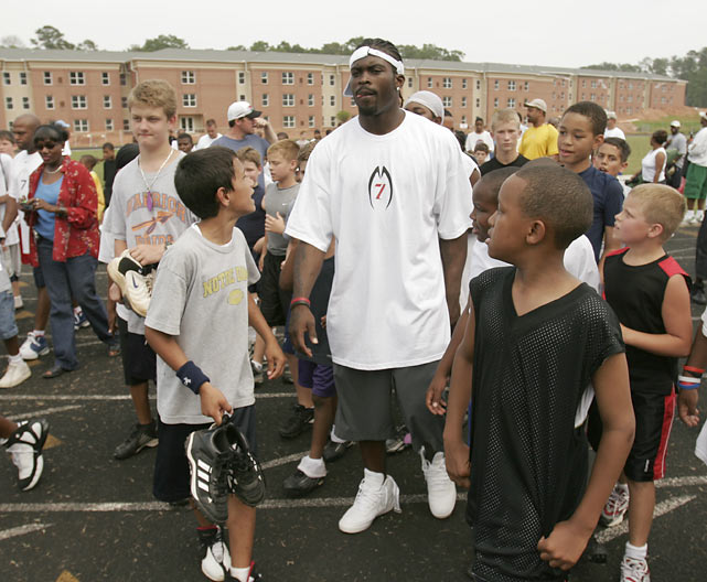 A group of children from the Michael Vick Football Camp walk with the quarterback after a morning workout.