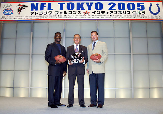 Vick poses with owner Arthur Blank and coach Jim Mora at a press conference in Tokyo before the NFL's annual American Bowl between the Falcons and Colts. Atlanta would win the preseason game, 27-21.