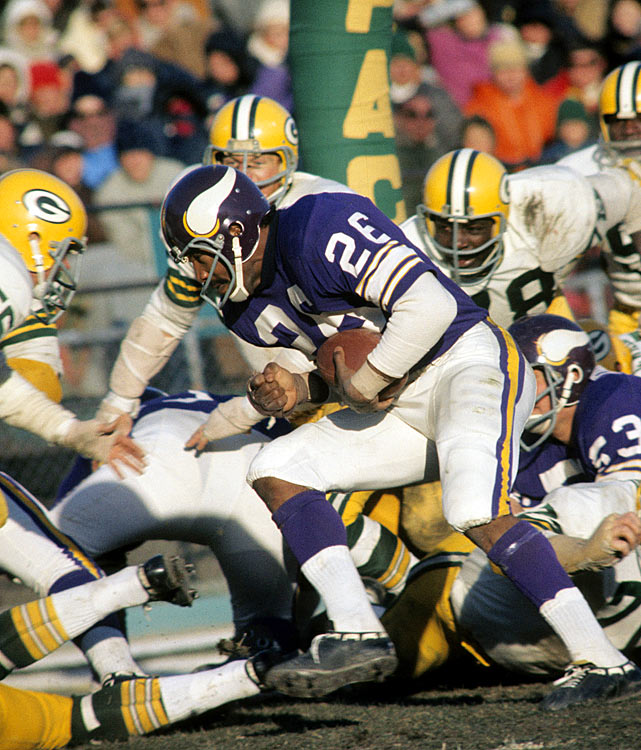 Plowing through the defending Green Bay Packers and into to the end zone is Minnesota running back Clint Jones. A goal-line specialist, Jones racked up nine touchdowns in 1970, despite tallying only 369 rushing yards.