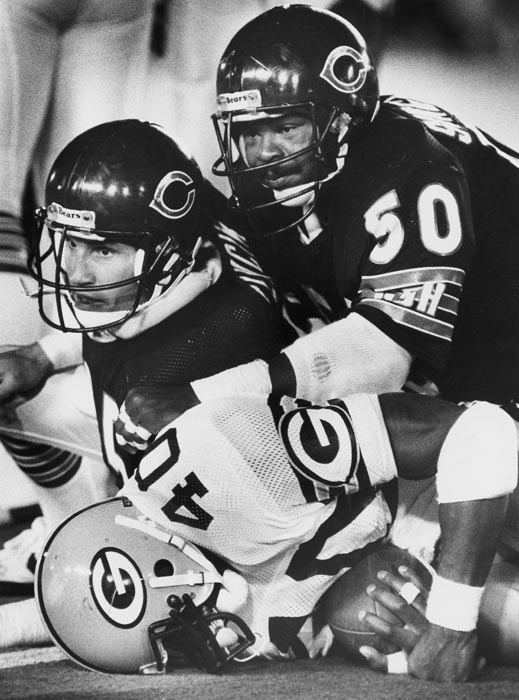 Gary Fencik and Mike Singletary tackle Green Bay's Eddie Lee Ivery during a victory over the Packers.