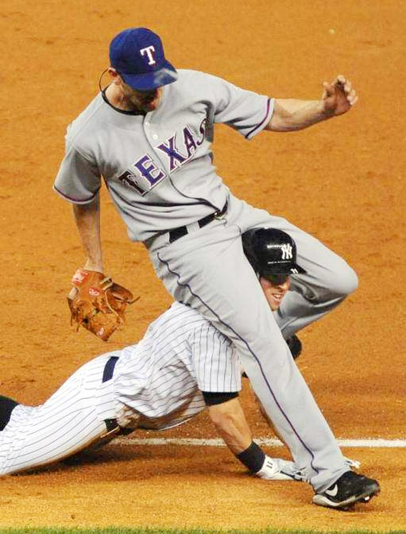 Brett Gardner of the New York Yankees slides through the legs of Texas Rangers pitcher Cliff Lee, who forced him out on a grounder in Game 3 of the ALCS on Oct. 18 in New York.  Texas won 8-0.