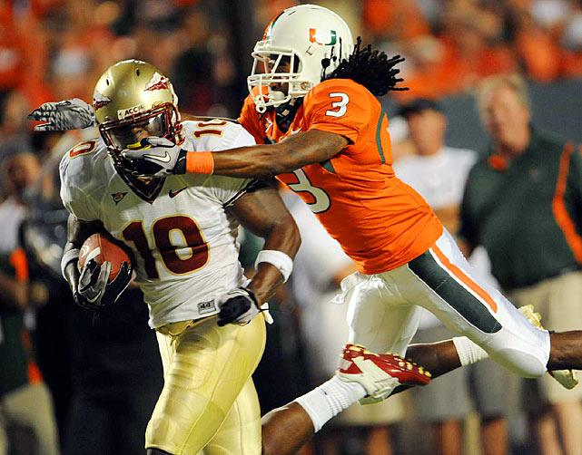 Florida State Seminoles safety Nick Moody gets a mouth full from Miami Hurricanes wide receiver Travis Benjamin as Moody attempts to return a fumble.  Florida State would defeat Miami 45-17.